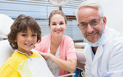 young boy sitting in dentist chair with mother and dentist all smiling together