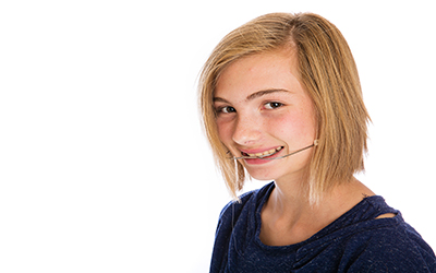 A young girl wearing orthodontic headgear