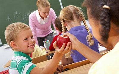 Children at school passing an apple in class