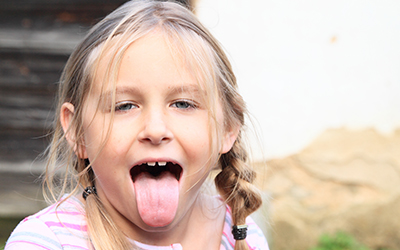 A young girl sticking her tongue out
